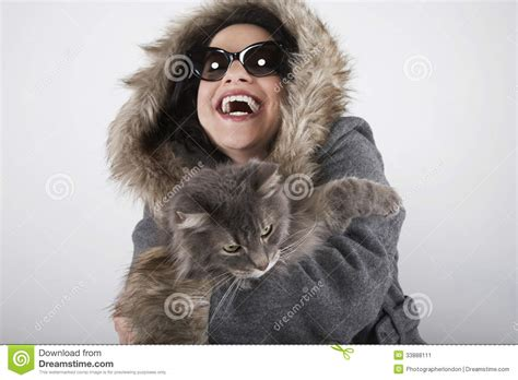 Laughing Woman In Hooded Fur Coat Holding Cat Stock Image